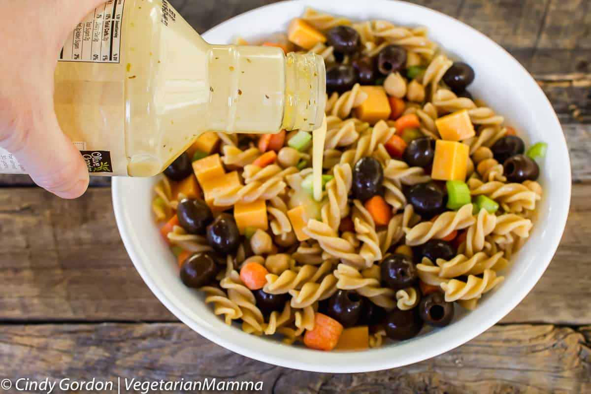summer pasta salad with dressing being poured