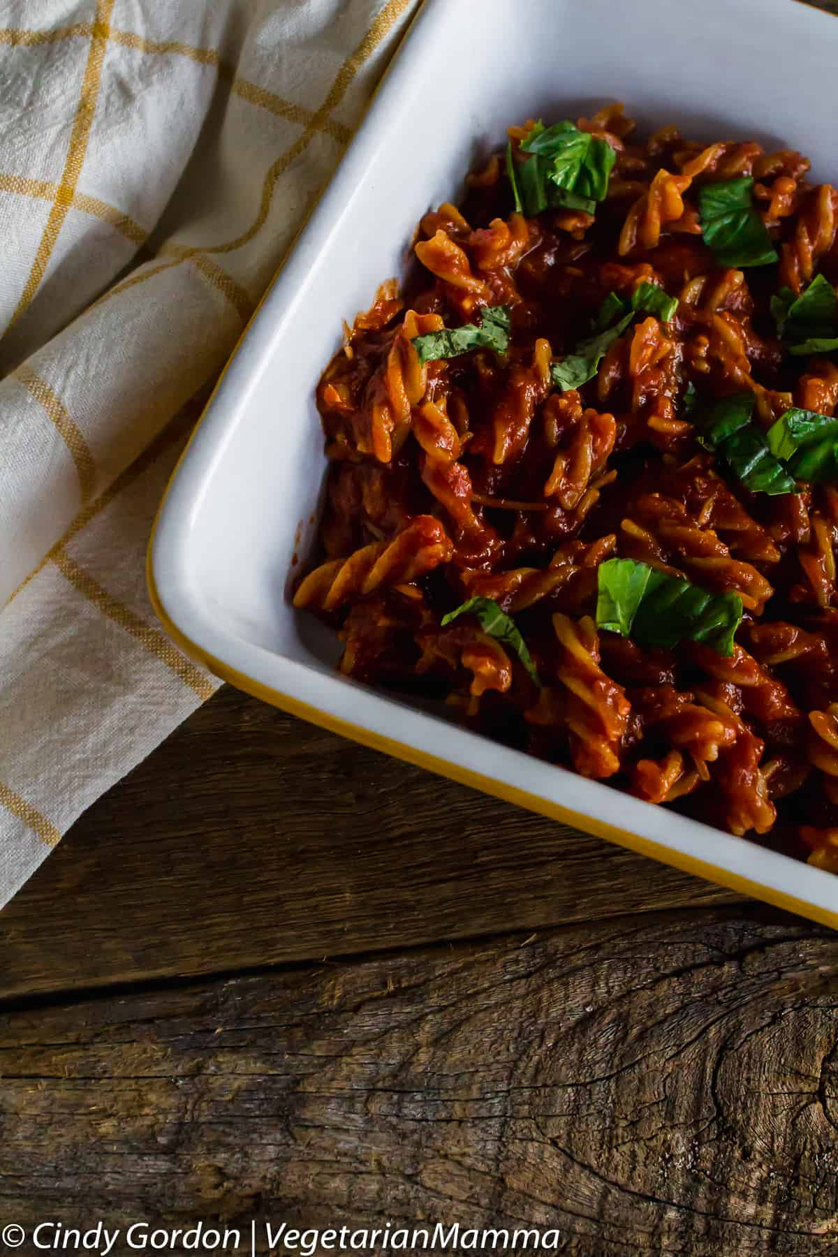 pasta coated in red sauce and topped with chopped bright green basil in a casserole dish on a wooden background
