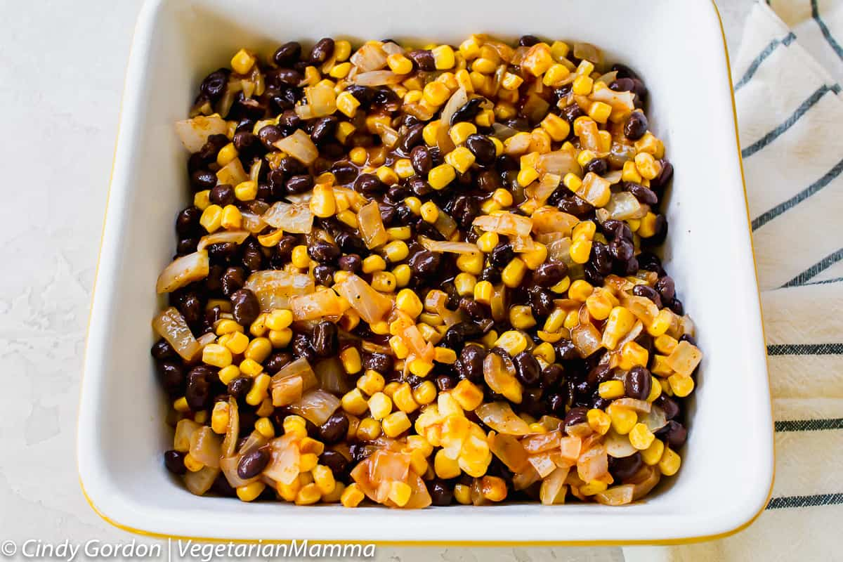 black bean, corn, and onion mixture on top of tater tots in casserole
