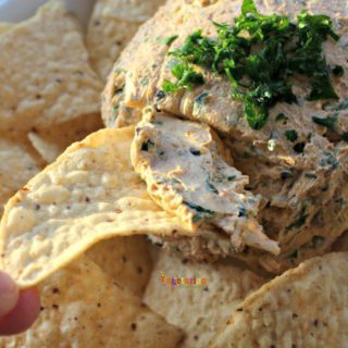 a tortilla chip scooping a portion from a round cheese ball topped with green herbs