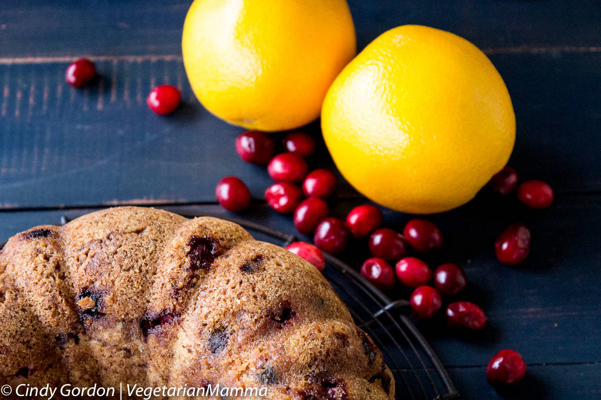 two oranges, cranberries and Gluten Free Cranberry Orange Cake