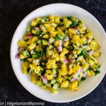 Top down view of Pineapple Salsa in white bowl atop black counter