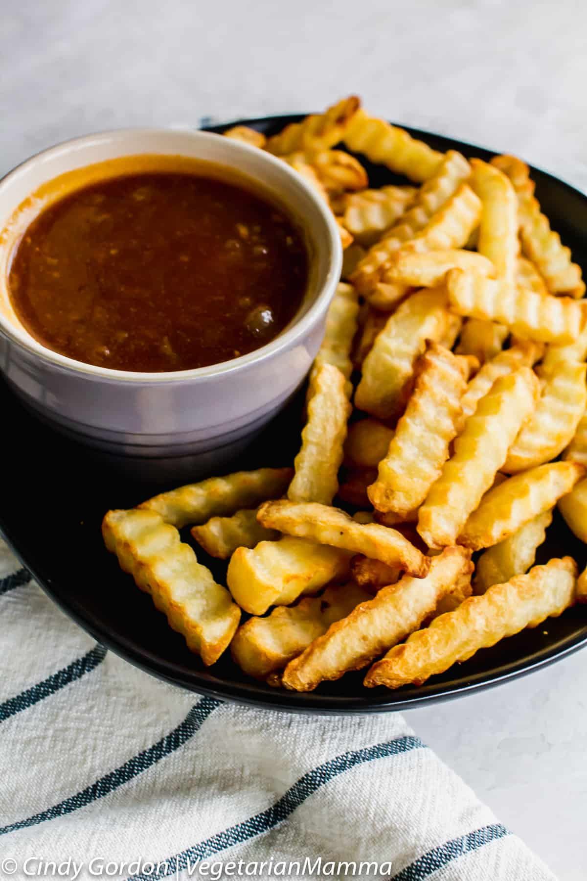 bowl of Dr Pepper BBQ Sauce on a plate with french fries
