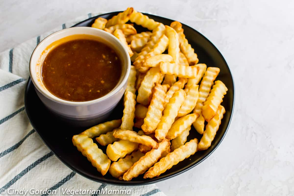 bowl of Dr Pepper barbecue Sauce on a plate with french fries