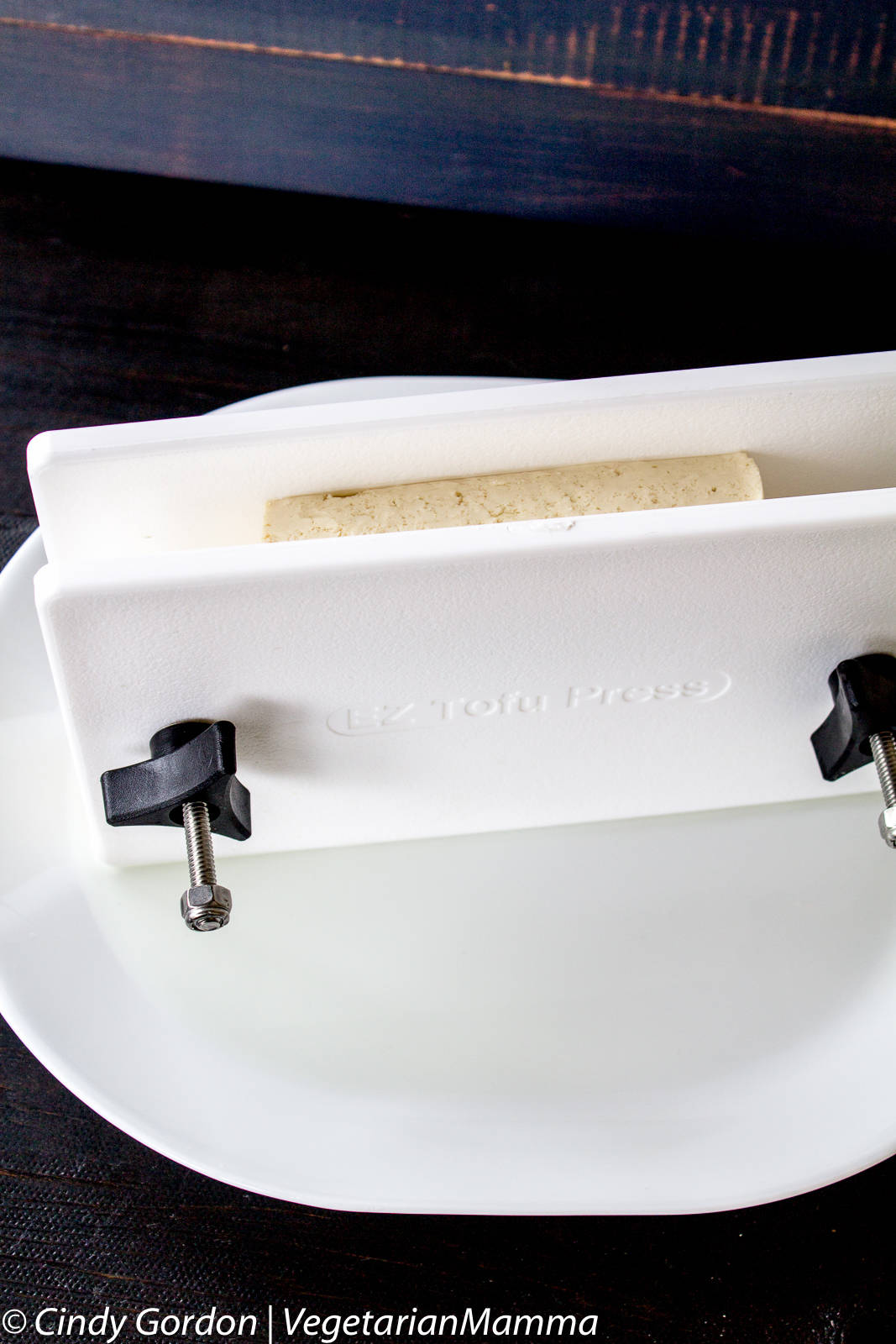 A white tofu press with a block of off white colored tofu inside