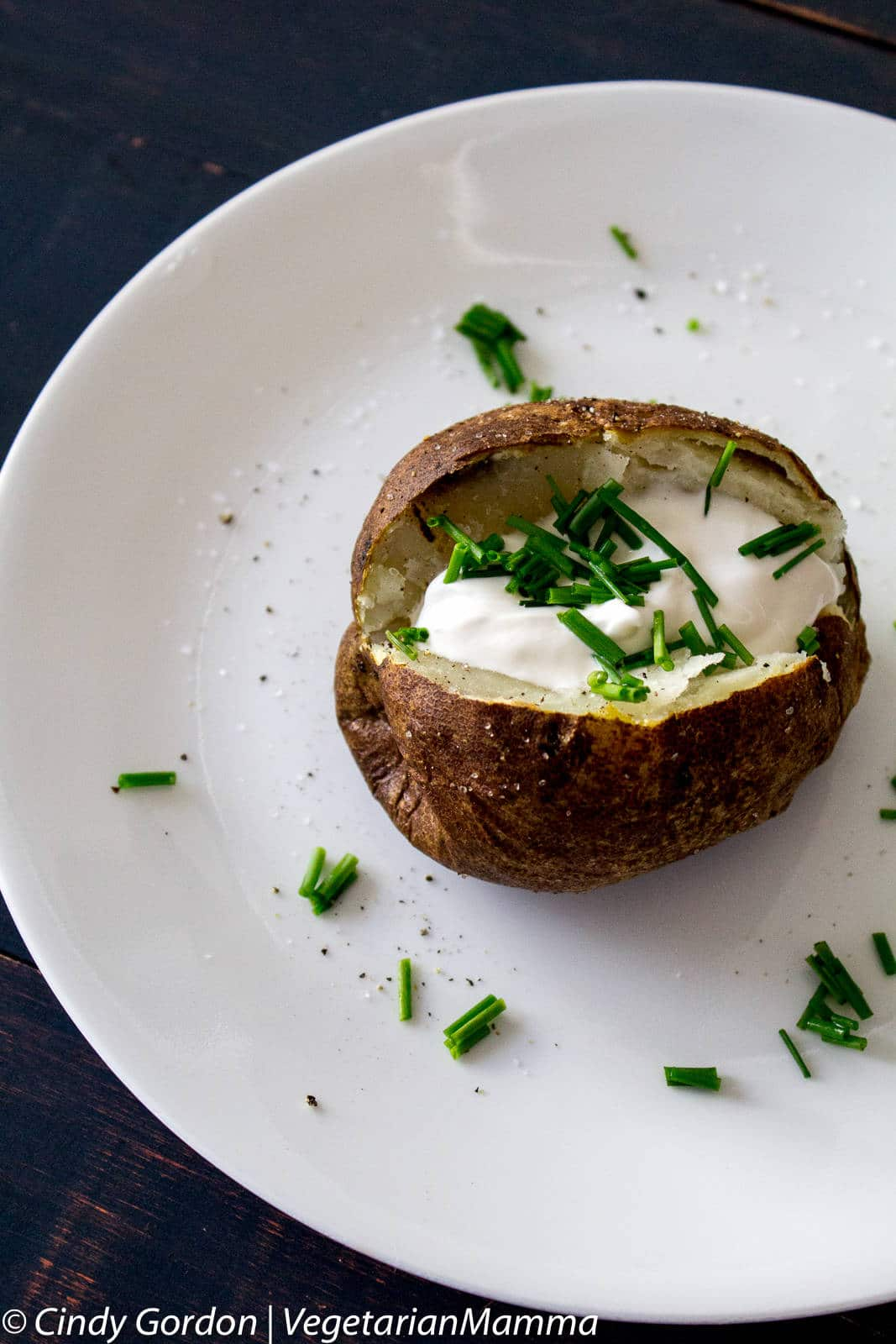 Air Fryer Baked Potato on a plate topped with sour cream and chives