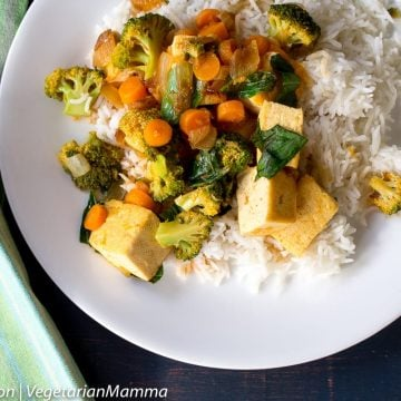 Curry Tofu with Broccoli and Rice in white plate atop black wooden pallet