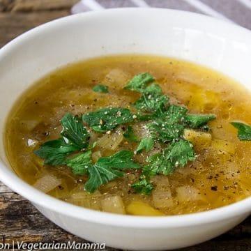 Instant Pot Potato Leek Soup in white bowl atop wooden pallet