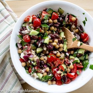 Mediterranean Chickpea Salad served in white bowl with striped cloth beside bowl