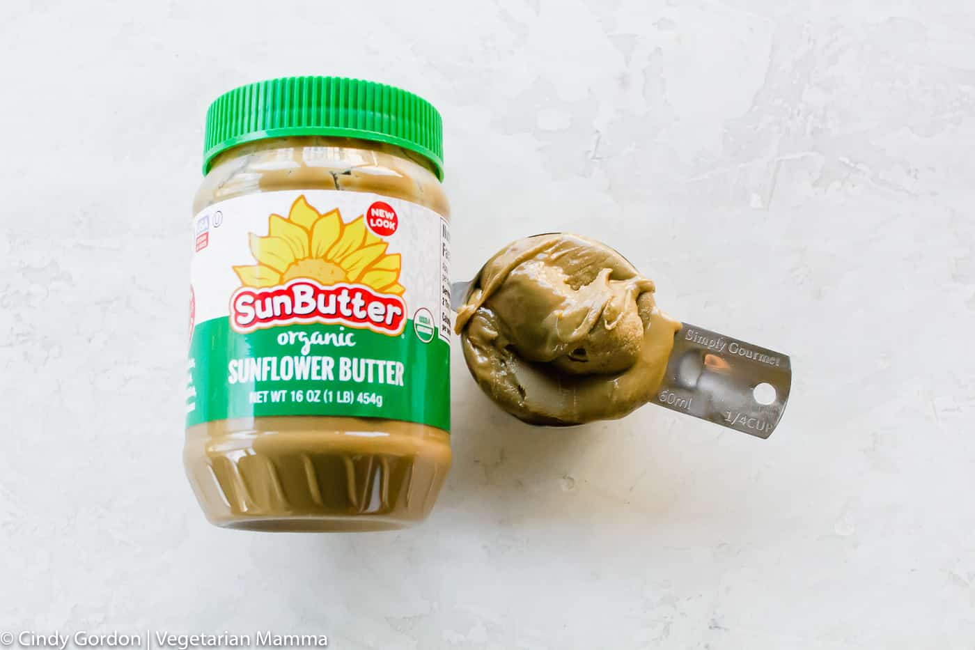 Organic SunButter pictured in jar and 1/4 measuring cup