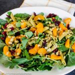 Pasta salad with spinach and mandarin oranges in white bowl
