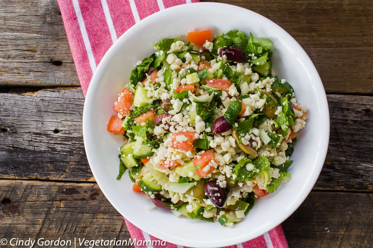 Gluten Free Allergy Friendly Cauliflower Tabbouleh is served in a white bowl on a wooden backdrop.
