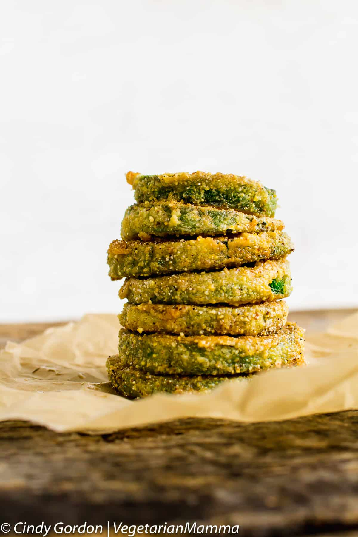 Crispy gluten free pan fried zucchini coins stacked up tall.