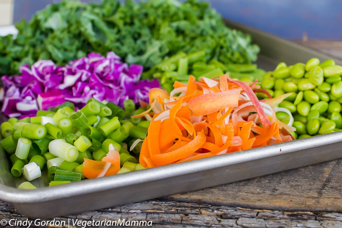 side view of ingredients for thai kale salad on a baking sheet
