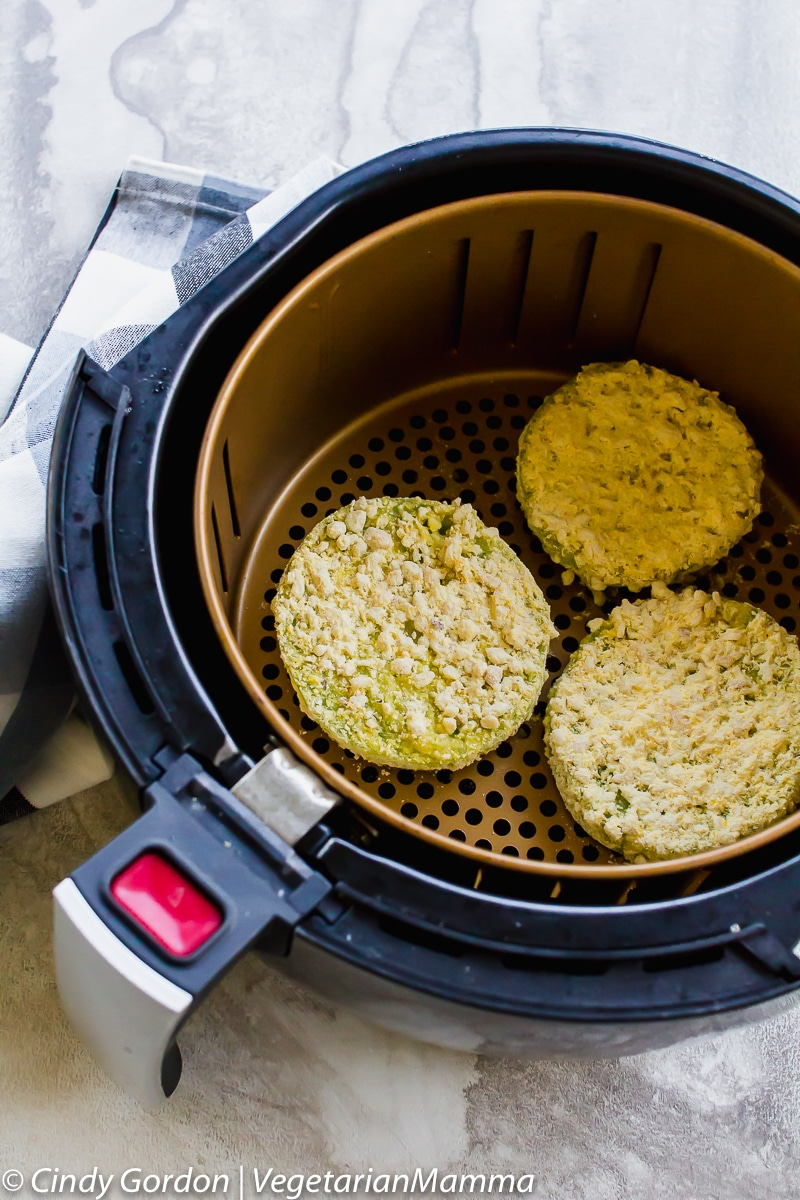 Air Fryer Fried Green Tomatoes in the air fryer basket.