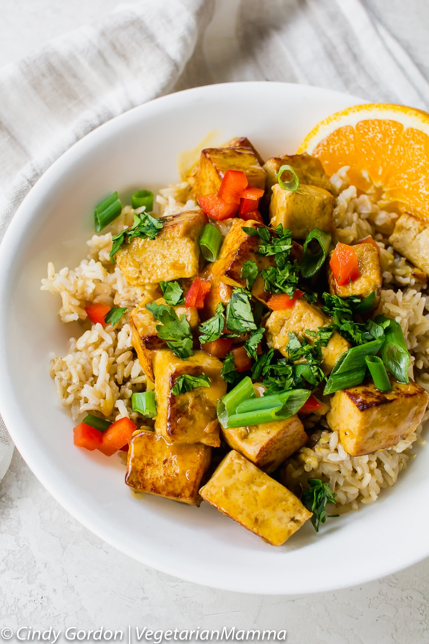 bowl of orange tofu served over rice