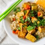 Orange Tofu in bowl with green chopstix to the side
