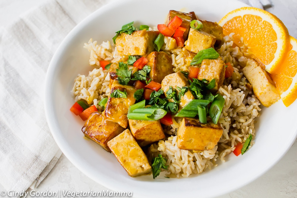 Bowl of Orange Tofu served with rice and orange slices.