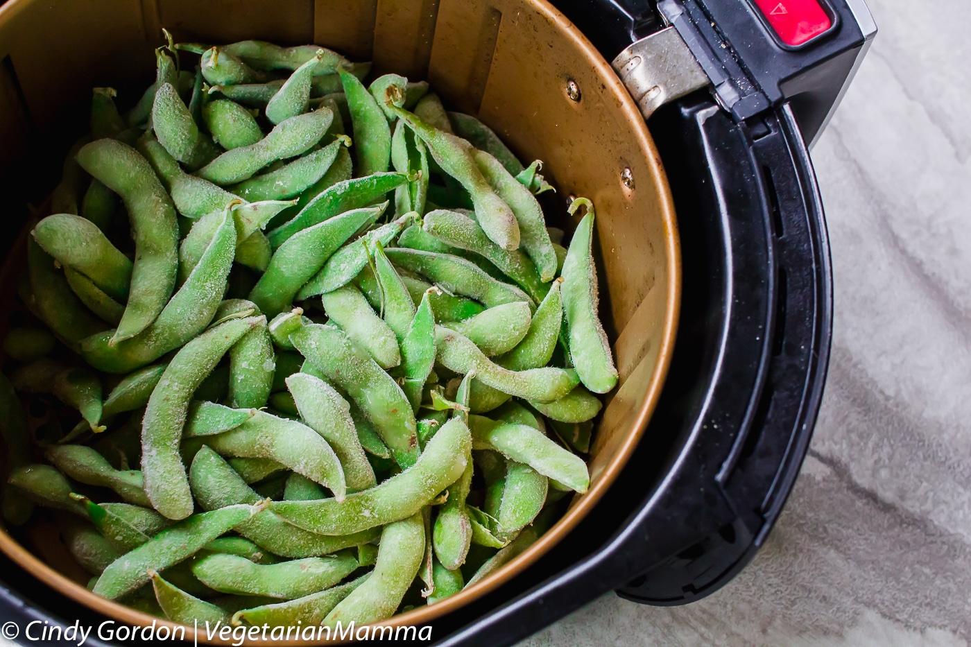 Frozen Edamame in the air fryer basket.