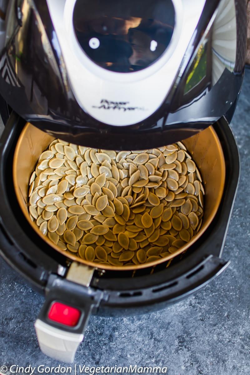 Air Fryer Pumpkin Seeds in the air fryer with basket open.