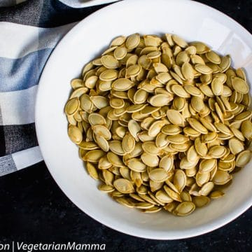 Top down view of pumpkin seeds inside of round white bowl