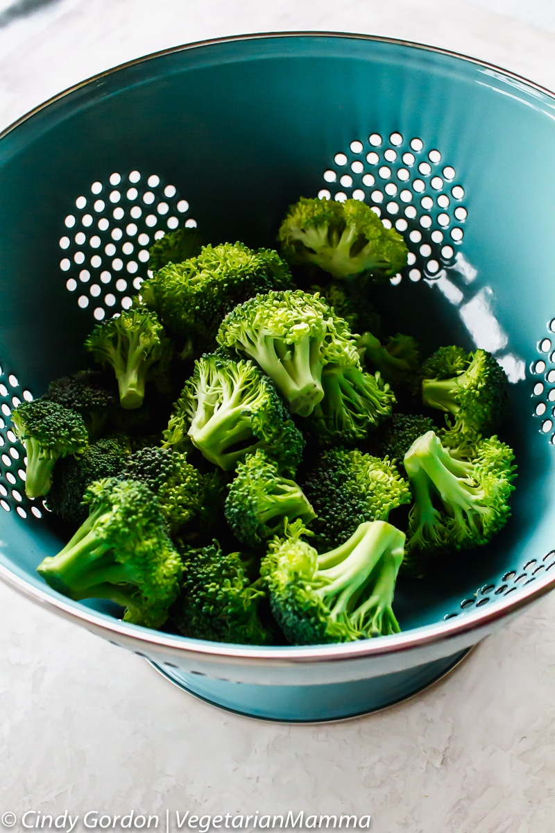 Air Fryer Broccoli - View of raw broccoli in blue strainer
