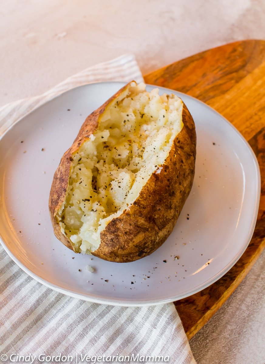 Air Fryer Baked Potato cut in half on a plate