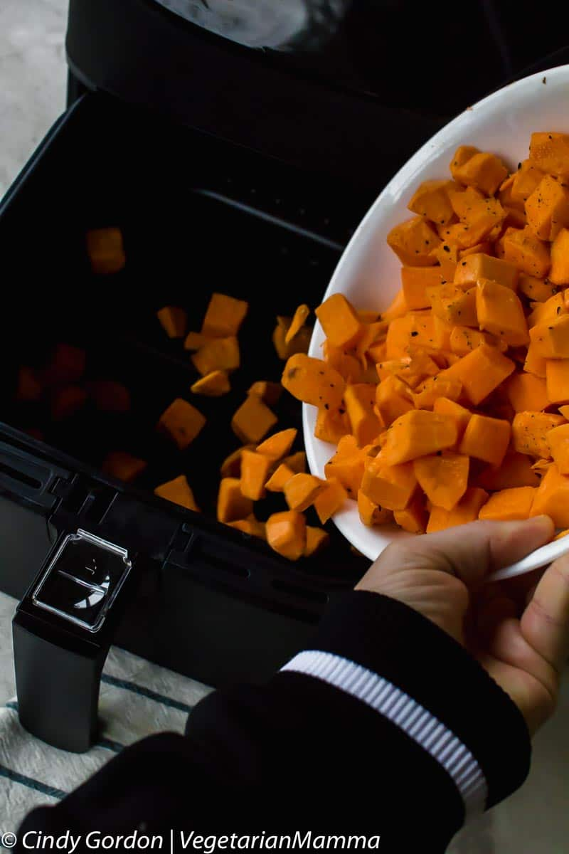 cubed sweet potatoes being tossed into air fryer basket