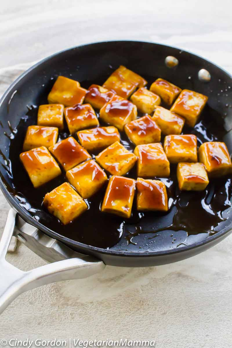 glazed brown tofu in a black skillet on a white board