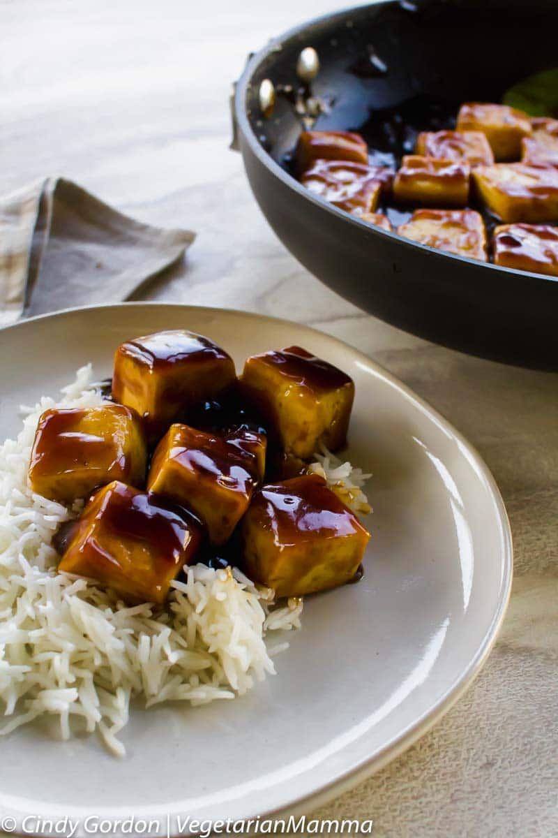 brown glazed tofu over rice on a white place with a black skillet in top right corner.