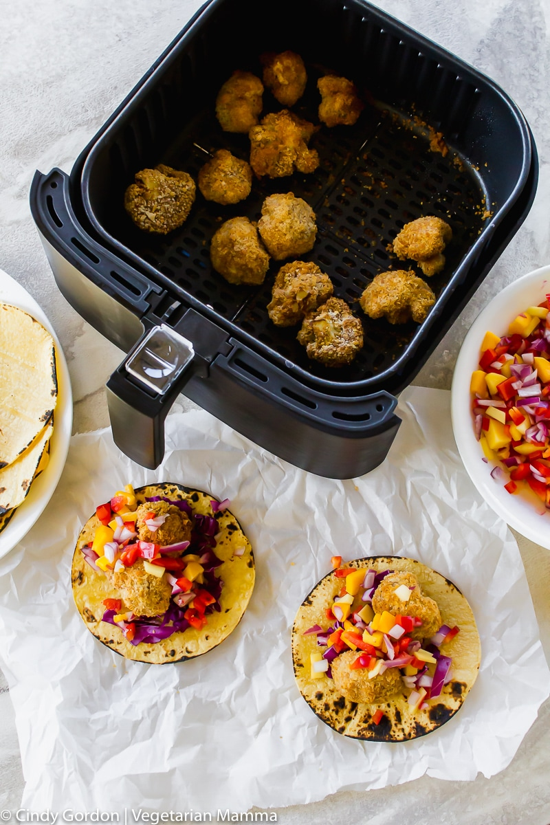 Over head shot of bread cauliflower bites in air fryer basket and corn tortilla tacos with cauliflower, purple cabbage and mango salsa