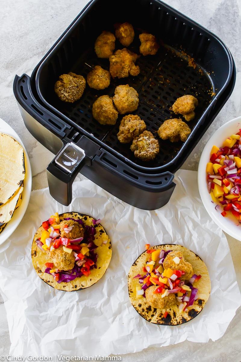 Over head shot of bread cauliflower bites in air fryer basket and corn tortilla tacos with cauliflower, purple cabbage and mango salsa