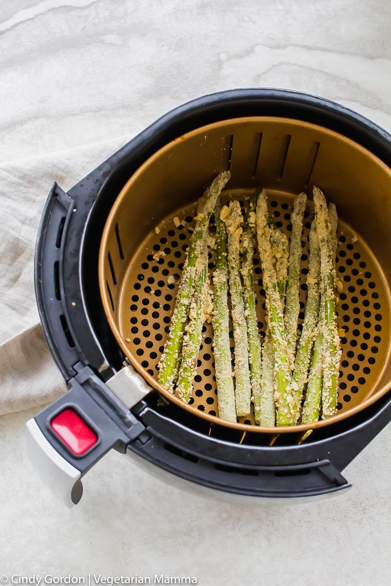 crispy coated asparagus in air fryer basket