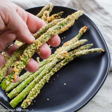 Hands holding Crispy Asparagus in Air Fryer