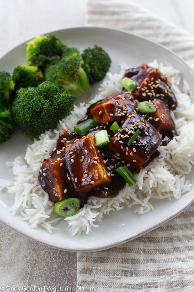 General Tso Tofu served over rice with bright green broccoli on a white plate