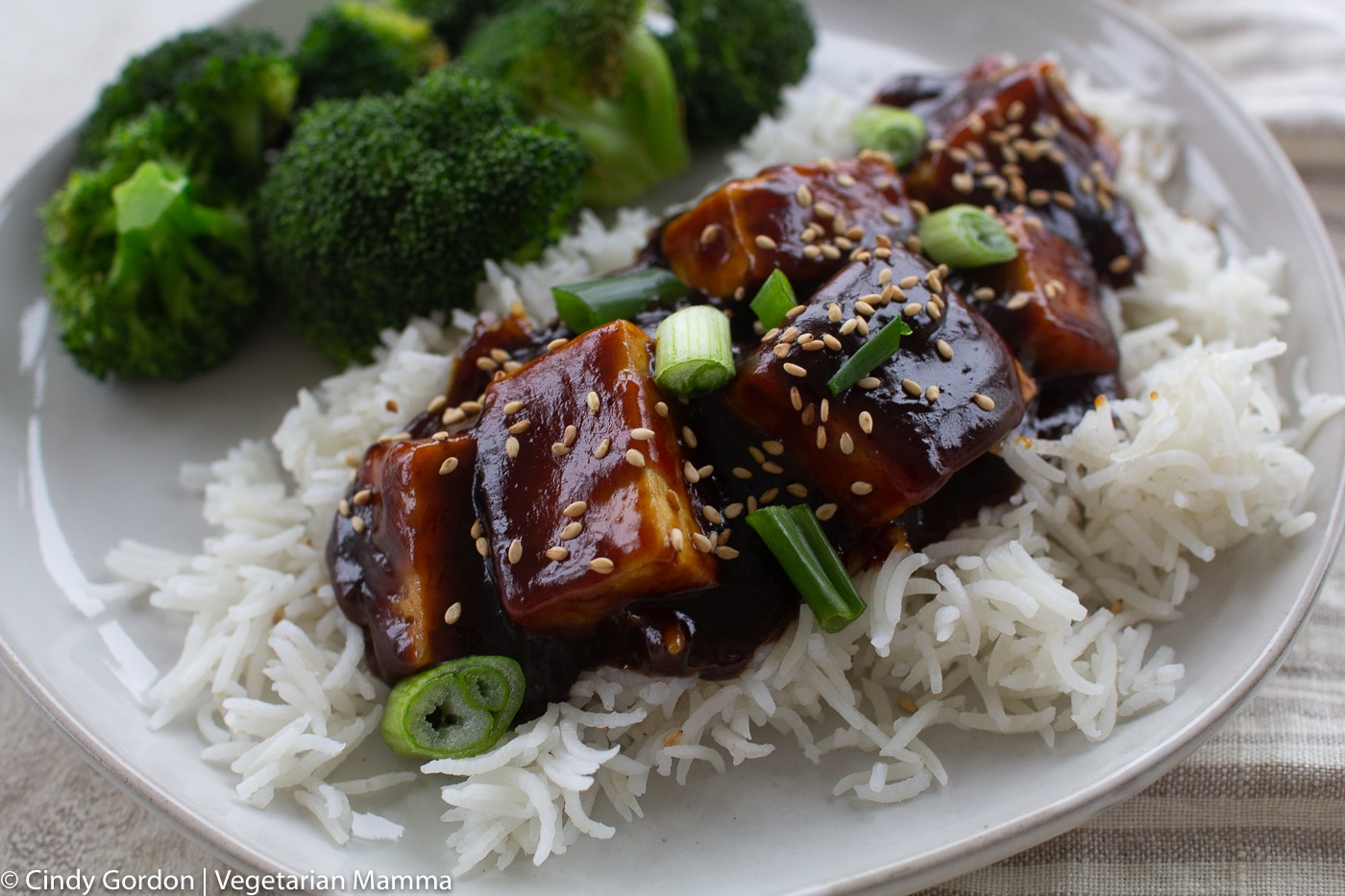 Saucy General Tso Tofu served over rice on a white plate