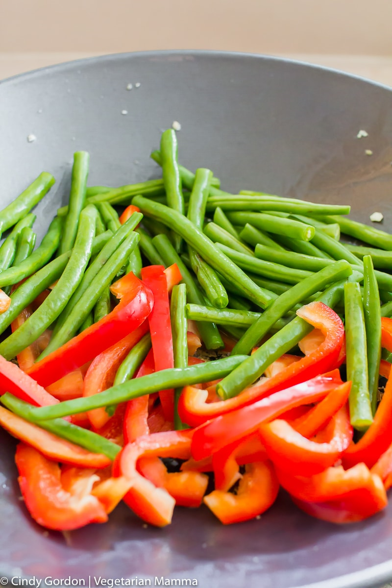 Green beans and red bell peppers slices in a black wok
