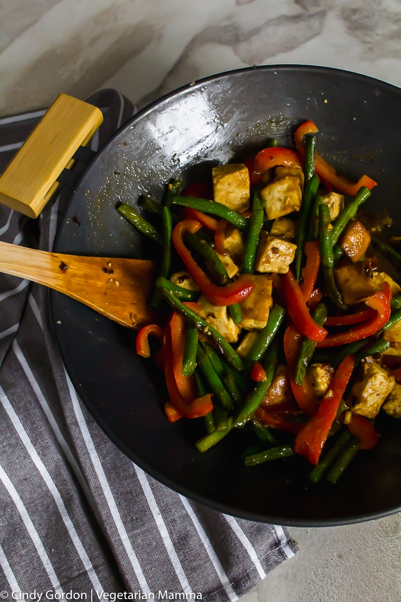 Overhead shot of the cooked tofu teriyaki in a black wok pan with green beans and red bell peppers