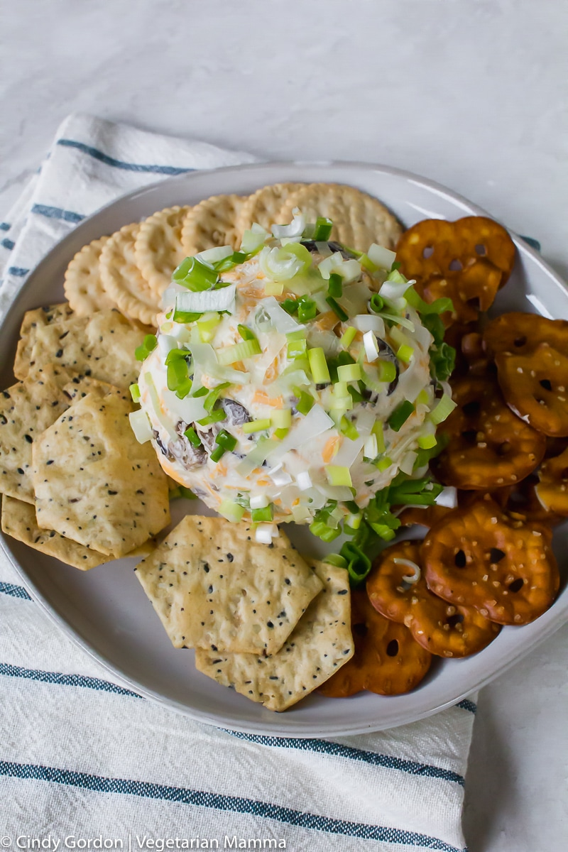 vegan cheese ball covered in diced green onions on a white plate with crackers and pretzels