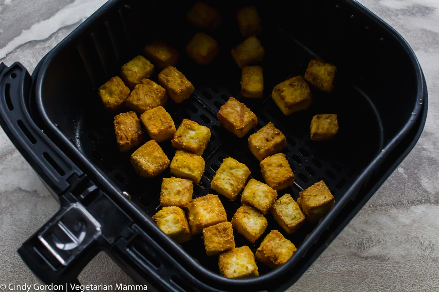crispy tofu pictured in air fryer basket