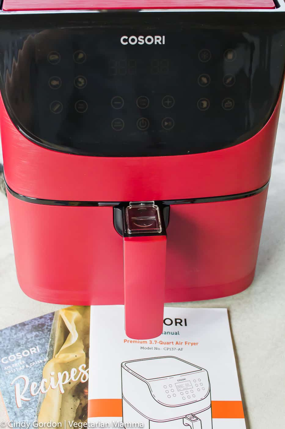 red cosori air fryer with instruction booklet