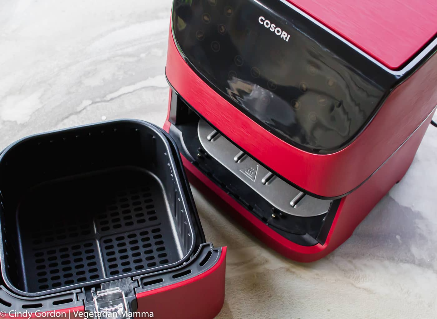 pictured is a red cosori air fryer with basket out of the unit