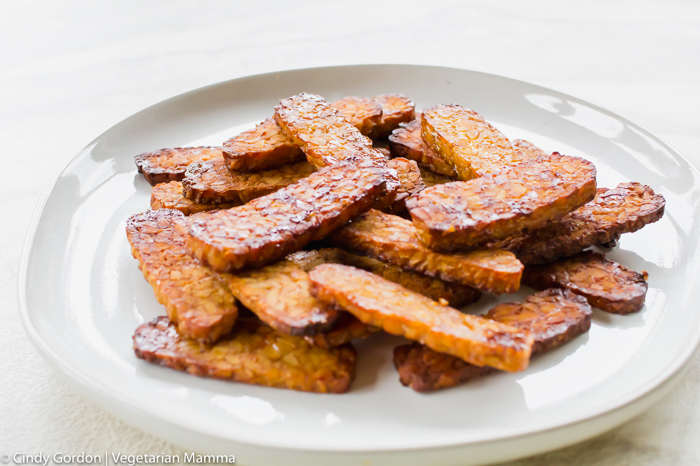Cooked vegan air fryer bacon on a white plate