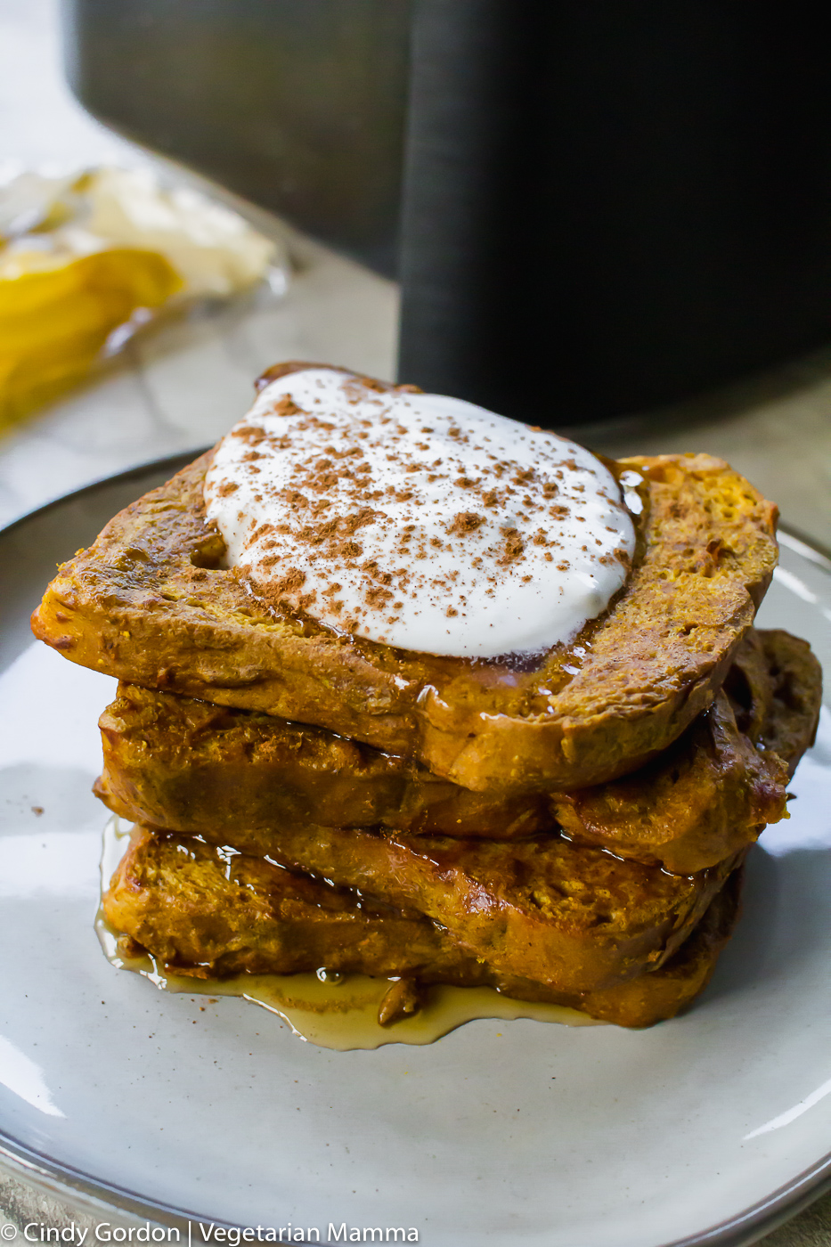 Pumpkin Air Fryer French Toast with whipped cream on top of staked bread