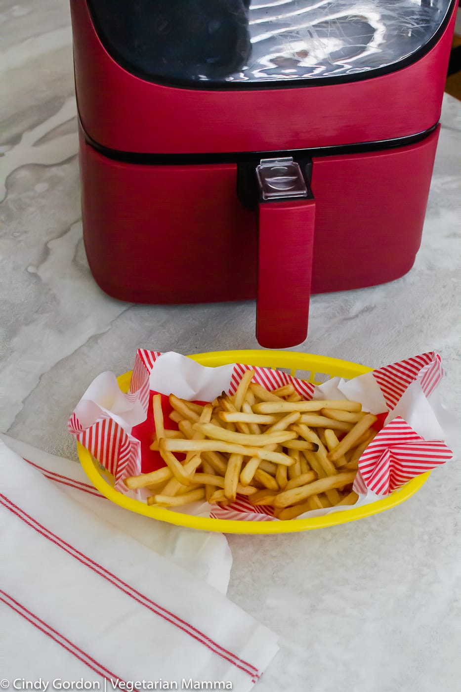 Air Fryer Frozen French Fries vertical photo showing red air fryer and cooked french fries