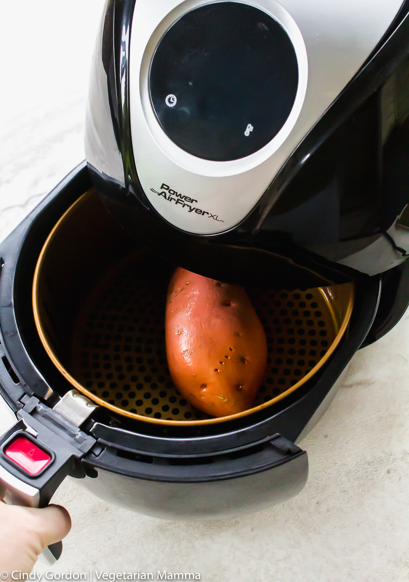 shot of an air fryer with a sweet potato in the air fryer basket