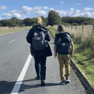 Woman and young boy walking along side of road