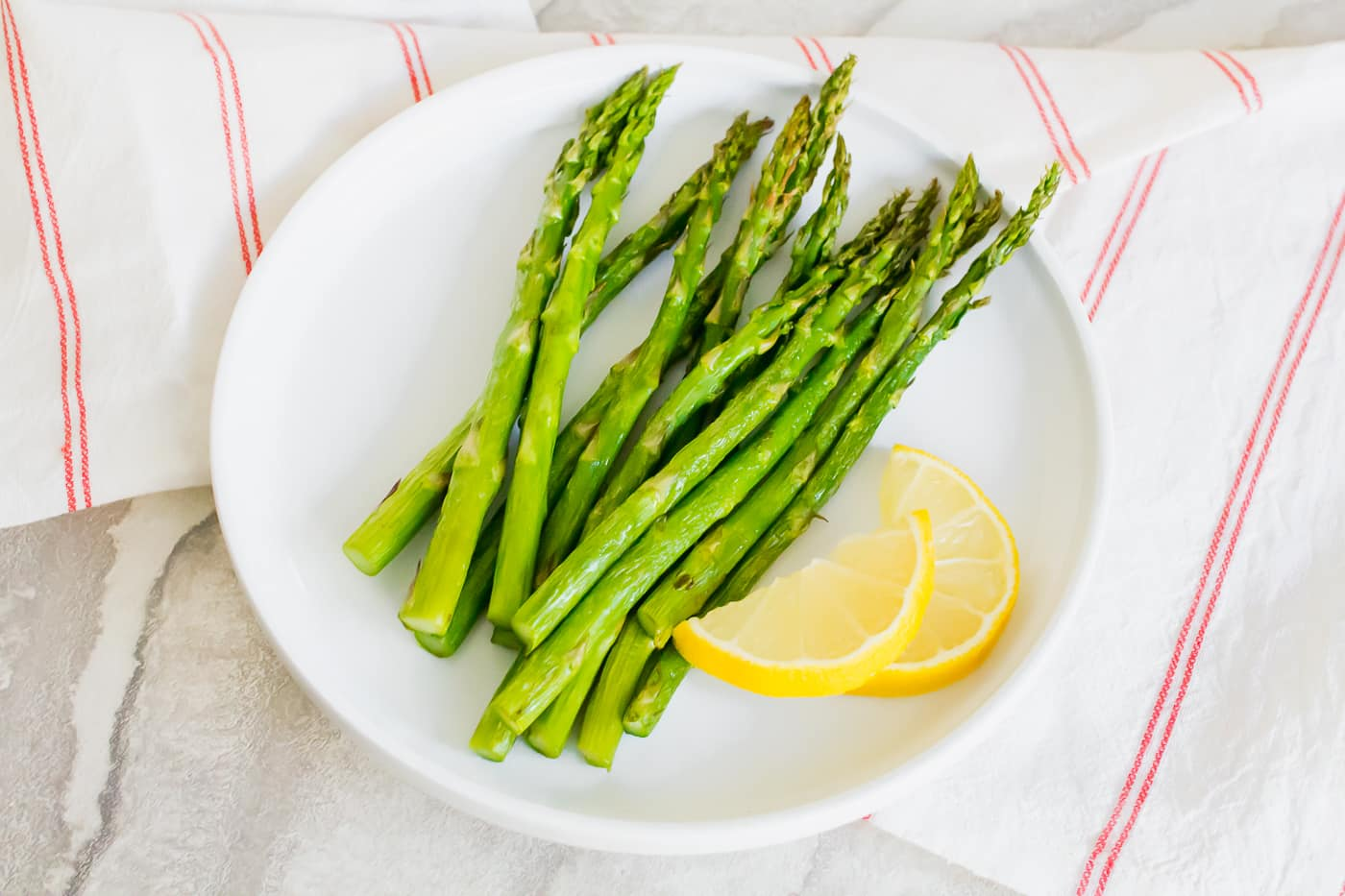 air fryer asparagus on a white plate with cut lemon on top of a white background