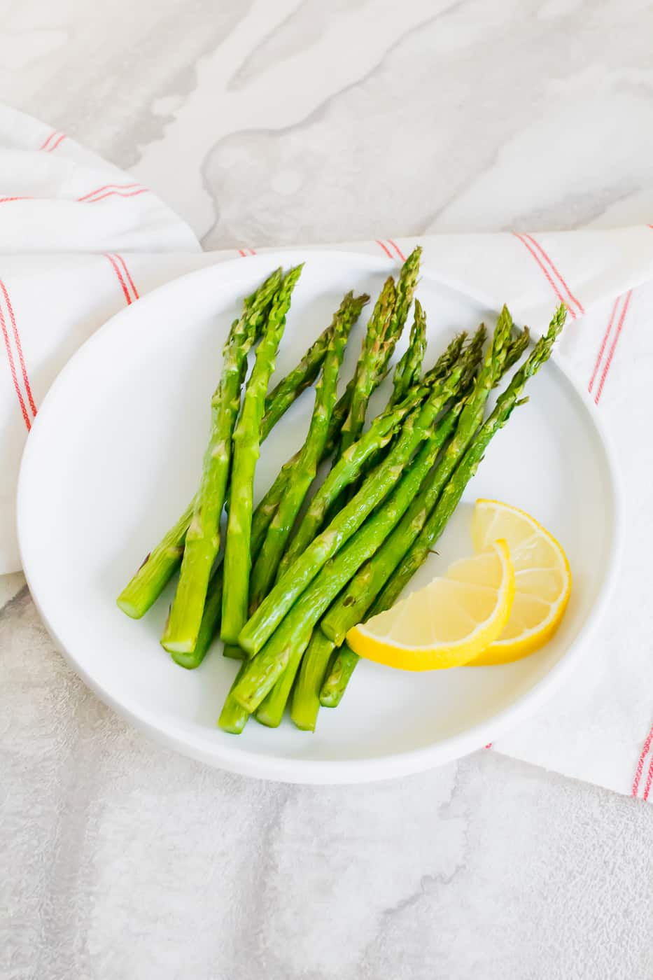 air fryer asparagus on a white plate with a yellow lemon cut in half