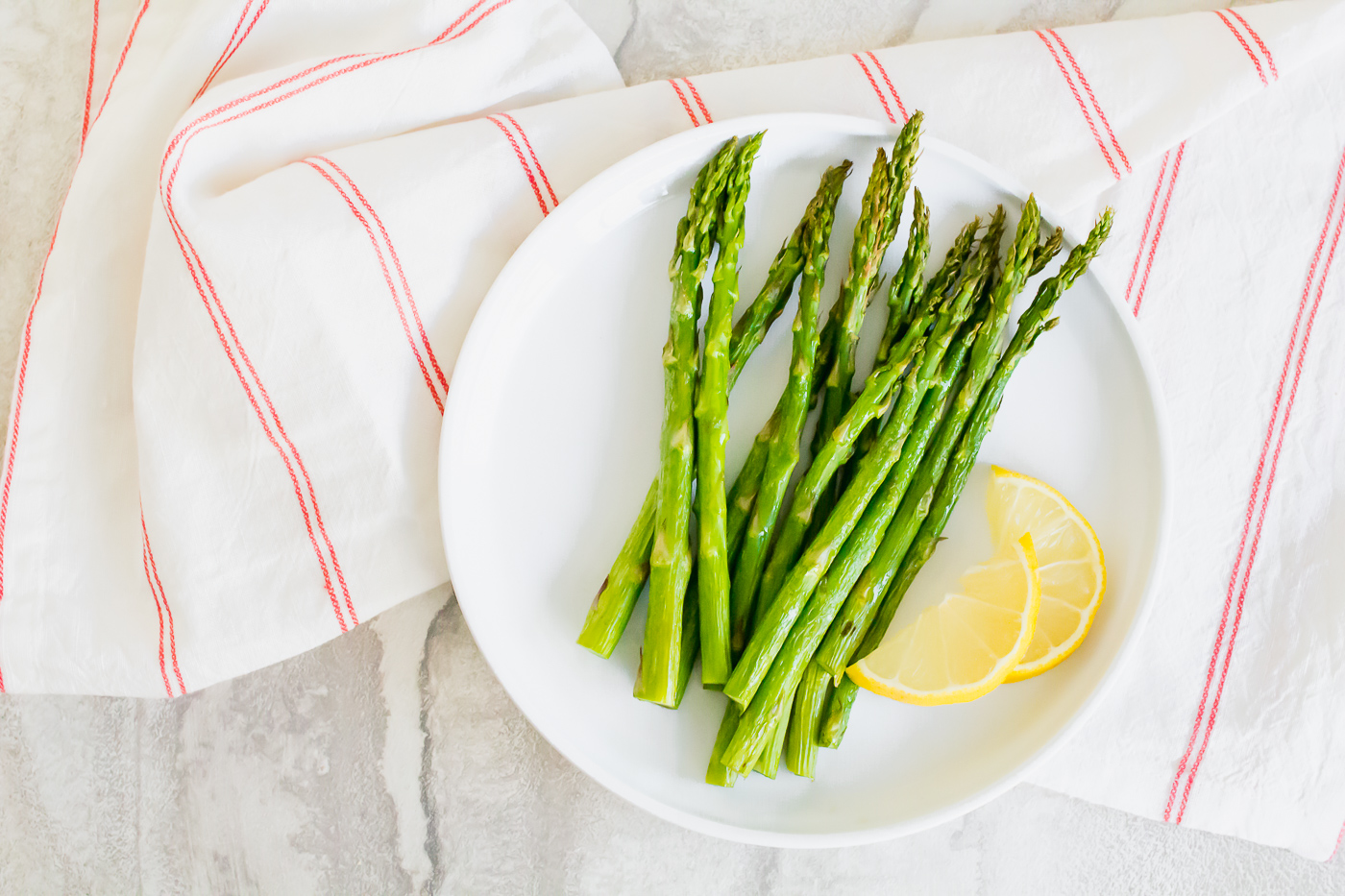 overhead shot of cooked air fryer asparagus on a white plate on top of a white and red striped napkin